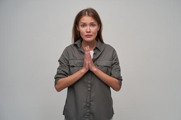 Adolescente, mulher infeliz com cabelo castanho comprido. vestindo camisa cinza e mantendo as palmas das mãos juntas, pede algo. assistindo a câmera isolada sobre fundo cinza