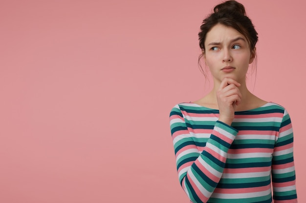Adolescente, mulher olhando curiosa com cabelo castanho e coque. vestindo blusa listrada e tocando seu queixo, sobrancelha erguida. observando à esquerda no espaço da cópia sobre a parede rosa pastel