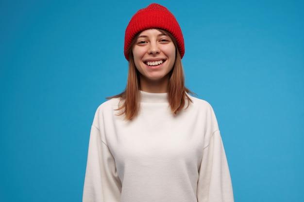 Adolescente, mulher olhando feliz com cabelo castanho. vestindo um suéter branco e um chapéu vermelho. tenha um grande sorriso. conceito de pessoas. isolado sobre a parede azul