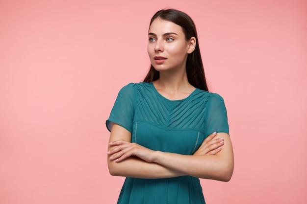 Adolescente, mulher olhando feliz com cabelo comprido morena. cruzando as mãos sobre o peito. usando um vestido esmeralda. observando à esquerda no espaço da cópia sobre a parede rosa pastel