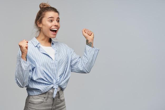 Adolescente, mulher olhando feliz com cabelo loiro reunido em um coque e tatuagens. vestindo camisa listrada com nó. ergue os punhos de empolgação. observando à direita no espaço de cópia sobre a parede cinza