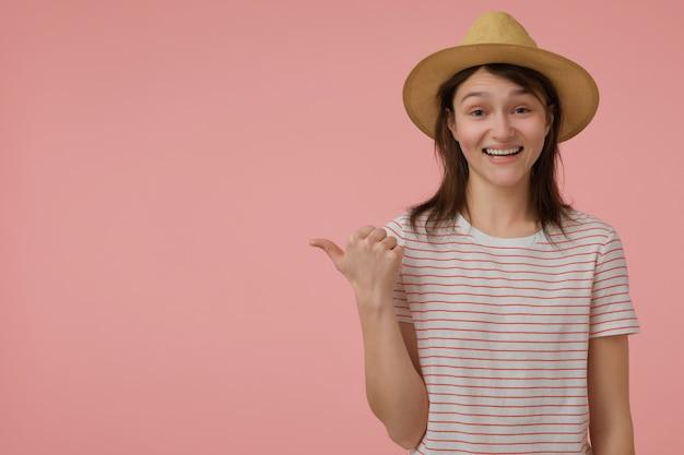 Adolescente, mulher olhando feliz com cabelo longo morena. usando uma camiseta com tiras vermelhas e um chapéu. apontando para a esquerda no espaço da cópia sobre a parede rosa pastel