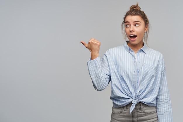Adolescente, mulher olhando surpresa com cabelo loiro reunido em um coque. vestindo camisa listrada com nó. apontando com o polegar e observando à esquerda no espaço da cópia, isolado sobre a parede cinza