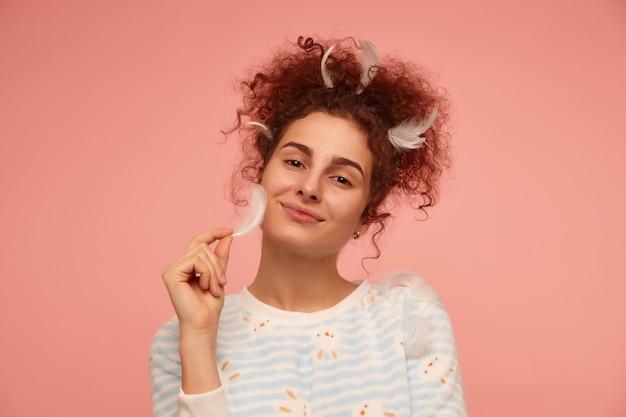 Adolescente, mulher ruiva com cabelo encaracolado. vestindo um suéter listrado com coelhos e tocando sua bochecha com penas. isolado, close up sobre parede rosa pastel