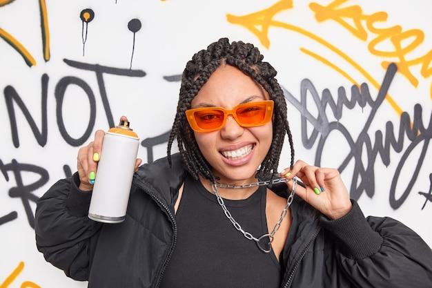 Adolescente na moda vestida com roupas pretas, óculos de sol laranja e corrente de metal trança poses de penteado com spray aerossol cria grafite criativo nas paredes da rua