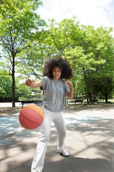 Adolescente negra sorridente jogando basquete