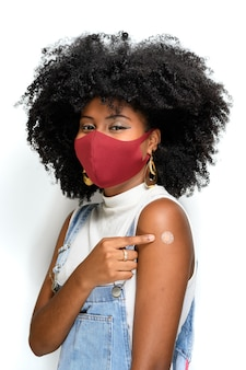Adolescente negro usando máscara protetora contra covid19 mostra a marca da vacina