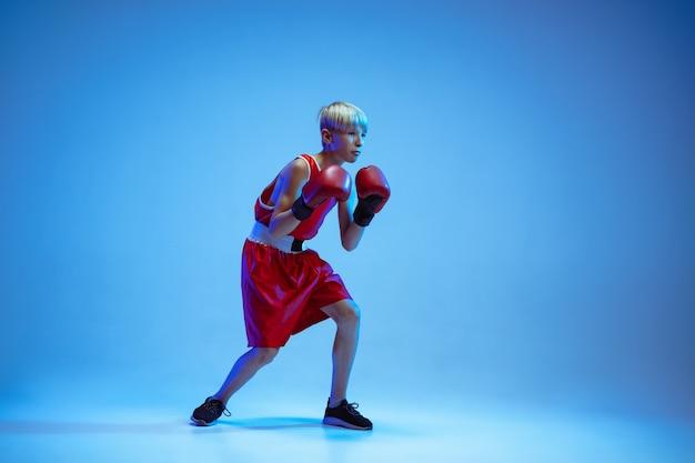 Adolescente no boxe sportswear isolado no fundo azul do estúdio em luz de néon. novato boxeador caucasiano masculino treinando duro e malhando, chutando. esporte, estilo de vida saudável, conceito de movimento.