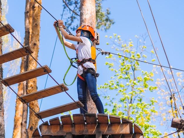 Adolescente no capacete laranja subindo nas árvores no parque de aventura na floresta.