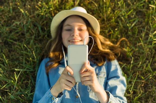 Adolescente no chapéu com fones de ouvido encontra-se na grama