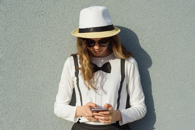 Adolescente no chapéu, garota usa smartphone