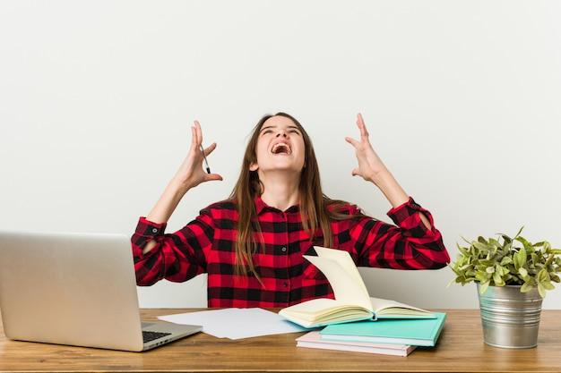 Adolescente novo que vai para trás a sua rotina que faz trabalhos de casa que grita ao céu.