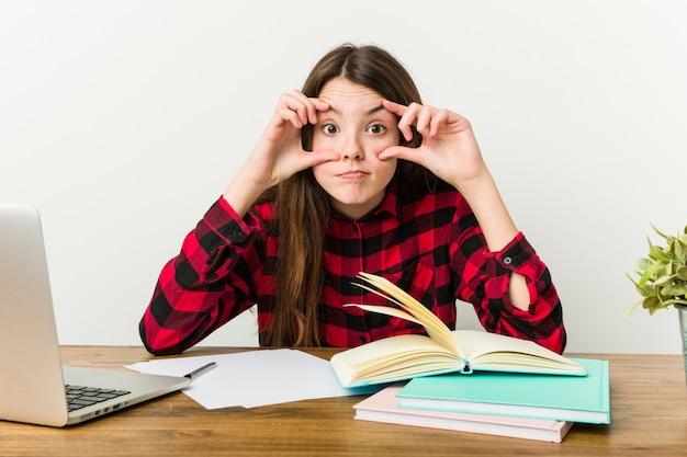 Adolescente novo que vai para trás a sua rotina que faz trabalhos de casa que mantêm os olhos abertos.