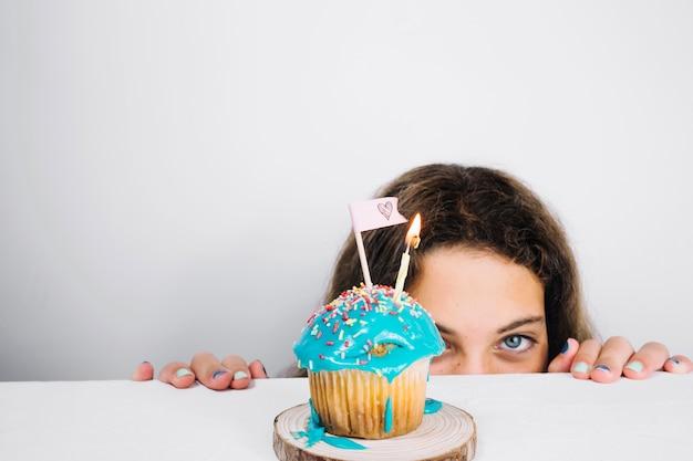 Adolescente olhando por trás da mesa com cupcake