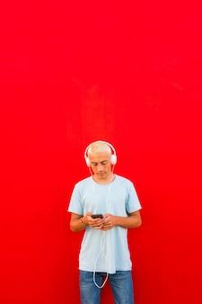 Adolescente ou homem usando seu telefone e ouvindo música com fones de ouvido com uma parede colorida vermelha ao fundo - conceito de estilo de vida musical - milenar online e adulto