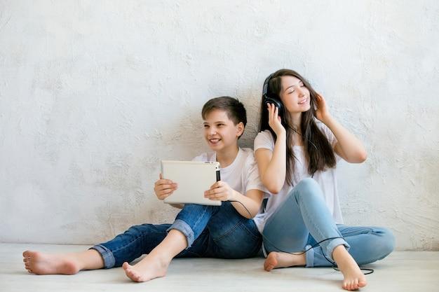 Adolescente ouve música sentada no chão ao lado do irmão com um tablet