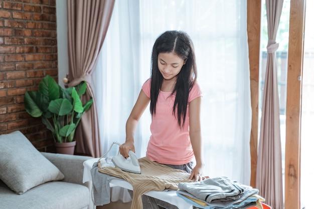 Adolescente passando roupas na tábua de passar no quarto em casa