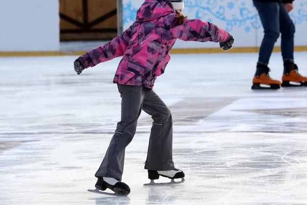 Adolescente patinando na pista de gelo