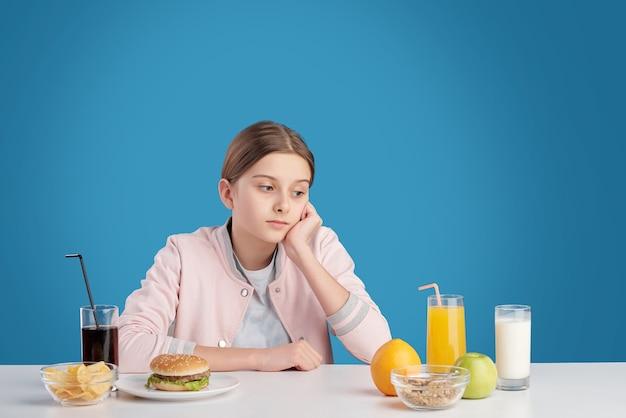 Adolescente pensativa sentada à mesa com alimentos saudáveis e não saudáveis e escolhendo a nutrição