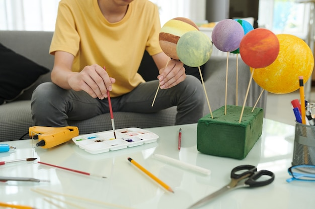 Adolescente pintando bolas de isopor ao fazer maquete do sistema solar para a escola