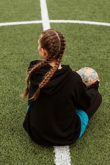Adolescente posando com uma bola ao ar livre