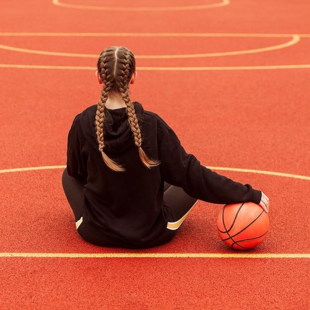 Adolescente posando no campo de basquete