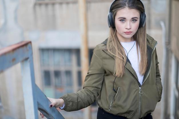 Adolescente posando ouvindo música usando fones de ouvido