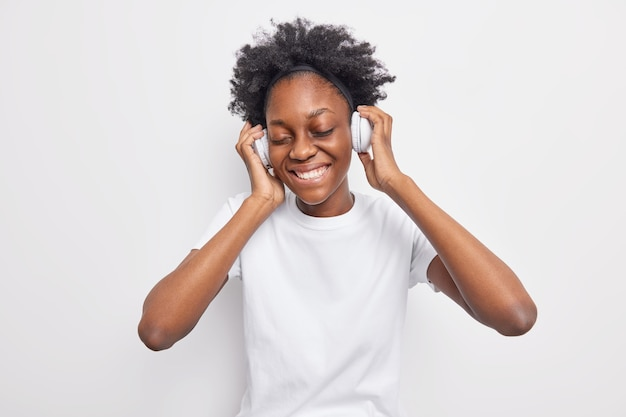 Adolescente positiva com cabelo encaracolado natural expressa emoções autênticas. sorri suavemente, mantém os olhos fechados e usa fones de ouvido estéreo, vestida com uma camiseta casual isolada no branco