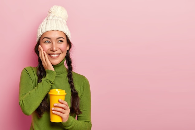 Adolescente positiva e sonhadora com tranças, toca as bochechas, lembra de algo muito agradável durante o intervalo para o café, segura um copo de bebida para viagem, usa chapéu de inverno e poloneck verde, posa sobre uma parede rosada