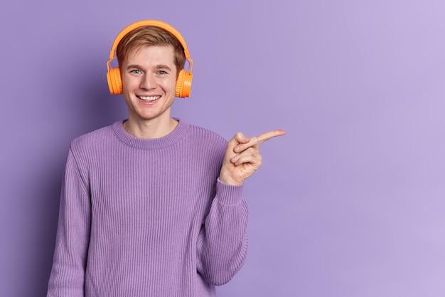 Adolescente positivo do sexo masculino com olhos azuis e sorriso feliz usa suéter roxo casual ouve música em fones de ouvido estéreo, pontos distantes no espaço da cópia, anuncia algo além do espaço da cópia. passatempo juvenil