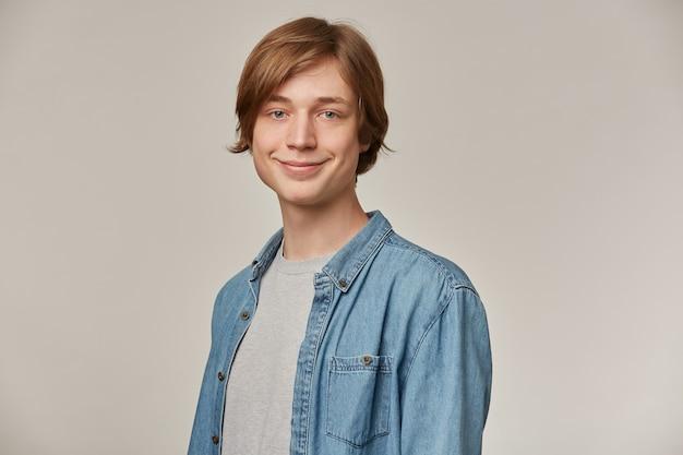 Adolescente positivo, homem de aparência feliz com cabelo loiro. vestindo camisa jeans azul. conceito de pessoas e emoção. assistindo e sorrindo isolado sobre uma parede cinza