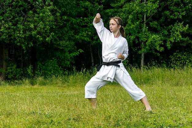 Adolescente praticando karate kata ao ar livre, executa o age-uke (bloqueio ascendente ou ascendente)