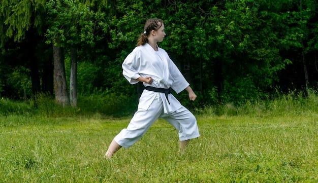 Adolescente praticando karatê kata ao ar livre, executando o gedan-barai ou bloqueio para baixo