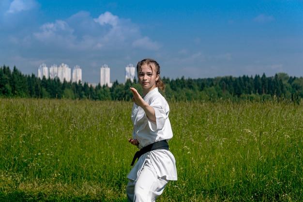 Adolescente praticando karatê kata ao ar livre, executando soto uke ou bloco externo