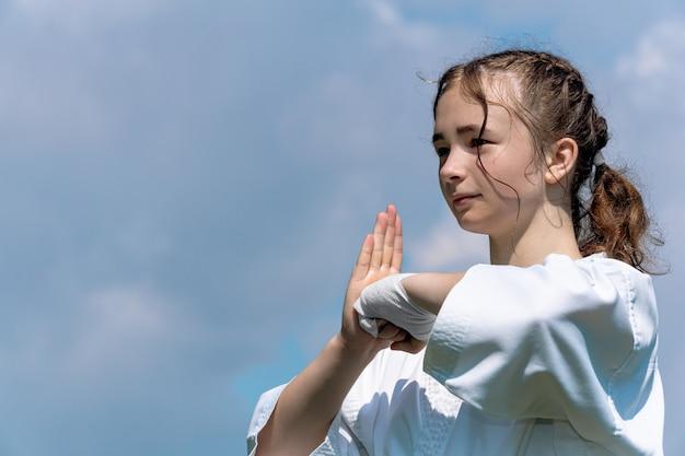 Adolescente praticando karatê kata ao ar livre, saudações oss