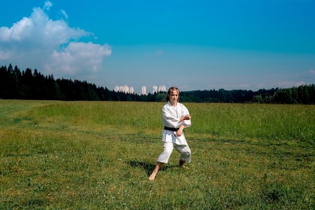 Adolescente praticando karatê kata ao ar livre se preparando para executar o bloqueio para baixo gedan barai