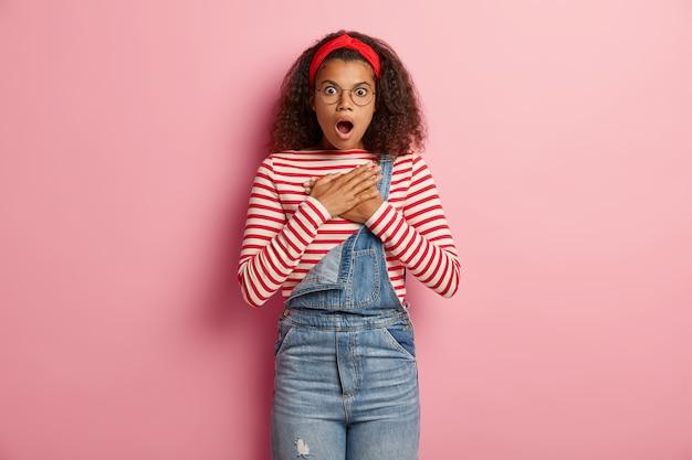 Adolescente preocupada posando de macacão com cabelo encaracolado