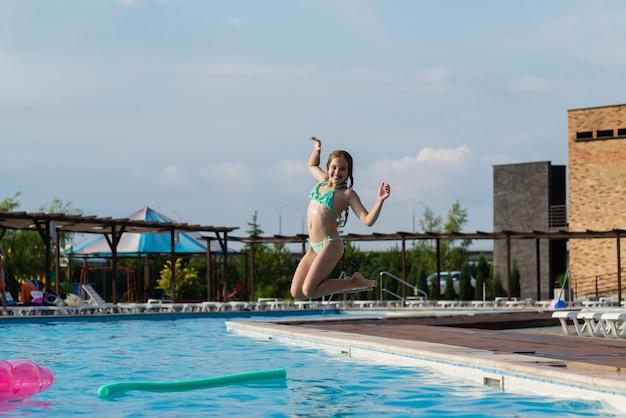 Adolescente pula na piscina