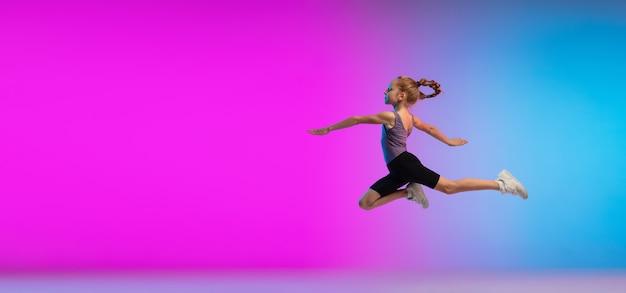 Adolescente pulando contra o fundo do estúdio gradiente de néon rosa azulado em movimento