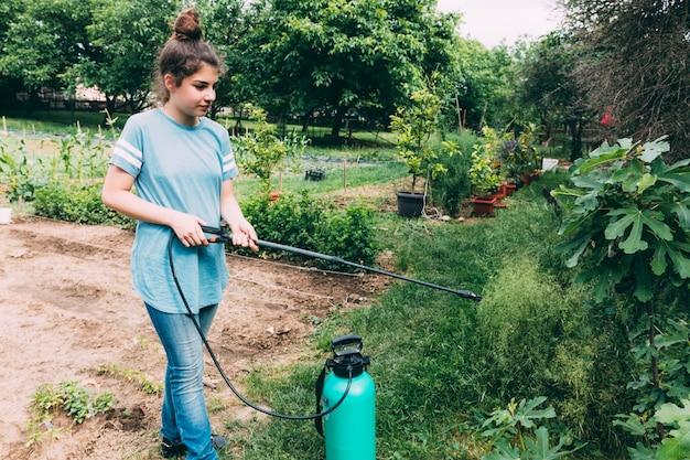 Adolescente, pulverização, plantas, em, jardim
