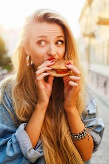 Adolescente que come um hambúrguer ao pôr do sol