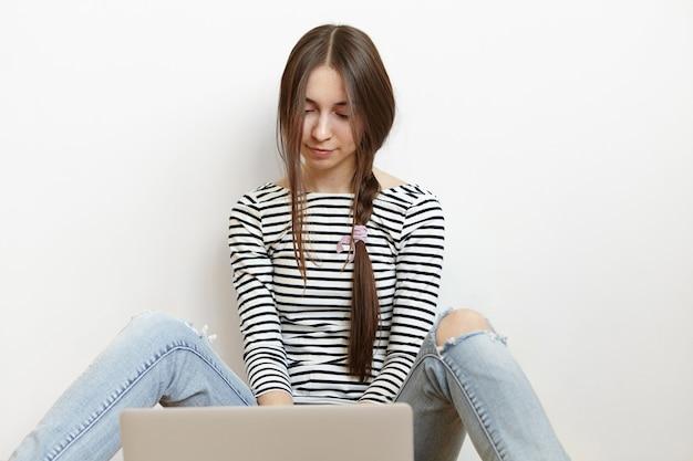 Adolescente relaxada vestida casualmente, sentada no chão em frente a um laptop aberto