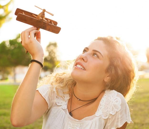 Adolescente relaxado que joga com seu avião ao ar livre