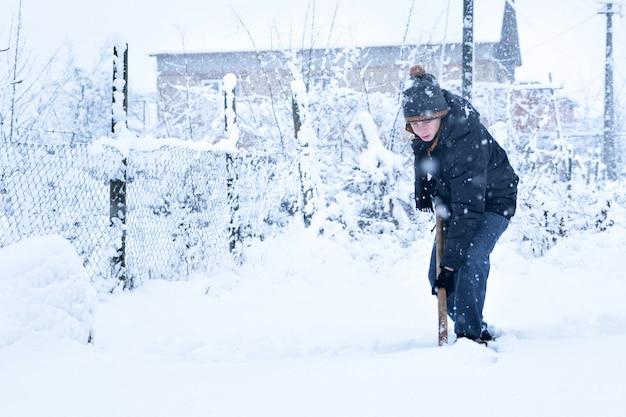 Adolescente, remover a neve com uma pá no inverno
