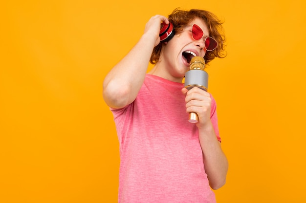 Adolescente ruiva em fones de ouvido ouve música e canta em um microfone amarelo