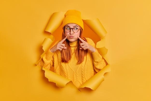 Adolescente ruiva engraçada prende a respiração e sopra as bochechas, aponta o dedo indicador no rosto parece de lado usa roupas de inverno.