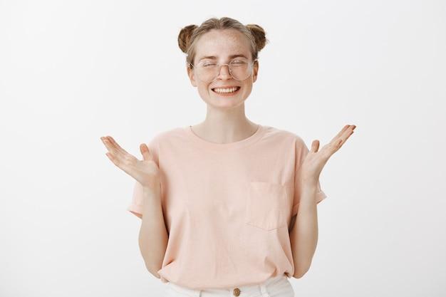 Adolescente ruiva feliz e bem-sucedida posando contra a parede branca