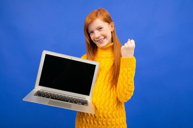 Adolescente ruiva feliz mostra uma tela de laptop para publicidade em azul