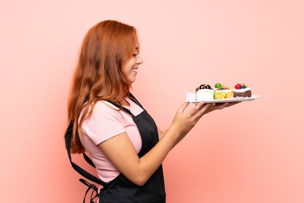Adolescente ruiva menina segurando lotes de diferentes mini bolos com expressão feliz