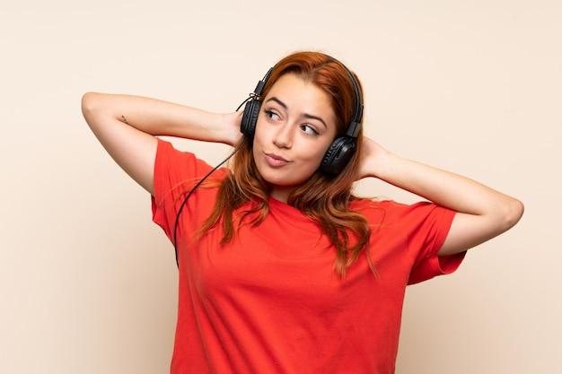 Adolescente ruiva ouvindo música sobre parede isolada